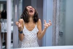 Angry woman shouting at mirror and crying