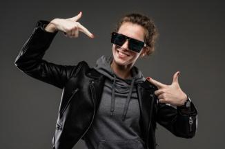 joven-rasgos-faciales-asperos-cabello-castano-manicura-brillante-bicicleta-gris-chaqueta-negra-gafas-sol-manos-presumir-dedos_88135-15351