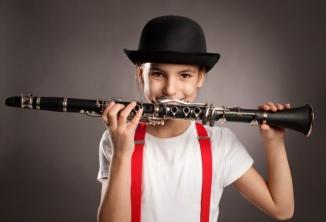 nina-tocando-clarinete-sobre-fondo-gris_127069-327